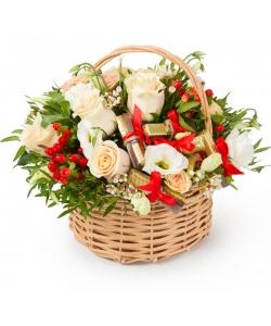 Корзина цветов из кремовых роз, белой эустомы, красного гиперикума, шоколадок и декоративной зелени с доставкой.