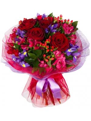Букет цветов из красных роз, розовой альстромерии, синих ирисов, гиперикума и декоративной зелени с доставкой.