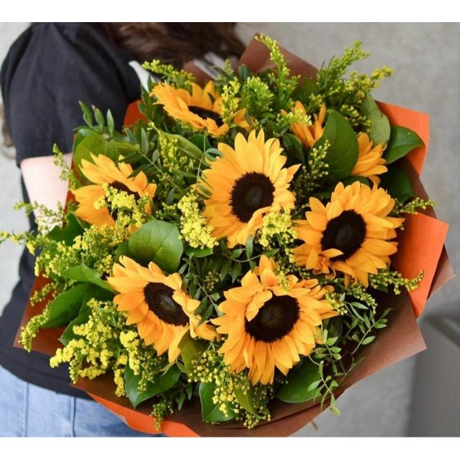 Букет цветов из оранжевых подсолнухов (7 штук, экстра класс) и декоративной зелени с доставкой по Киеву.